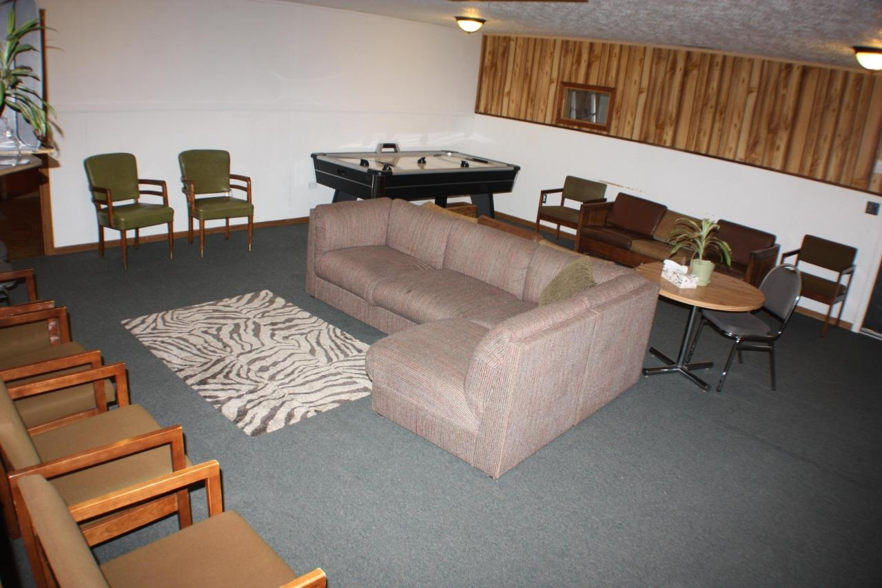 community living space with chairs, couch and air hockey