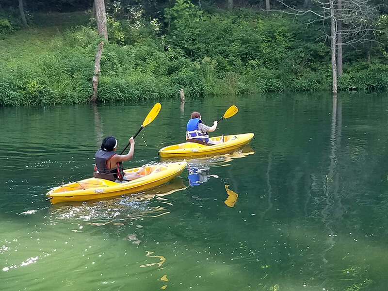 kids smiling and canoeing